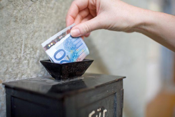 Een vrouw stopt geld in een brievenbus