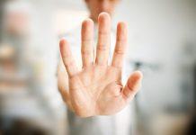 Een hand geeft een stopgebaar aan