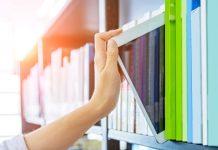 Vrouw pakt tussen de boeken in de boekenkast een tablet
