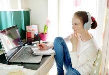 Jonge vrouw maakt aantekeningen achter laptop